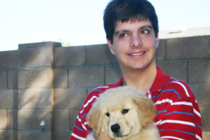 Young adult man holding golden retriever puppy