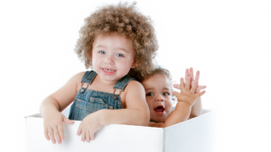two smiling toddler playing in a white box