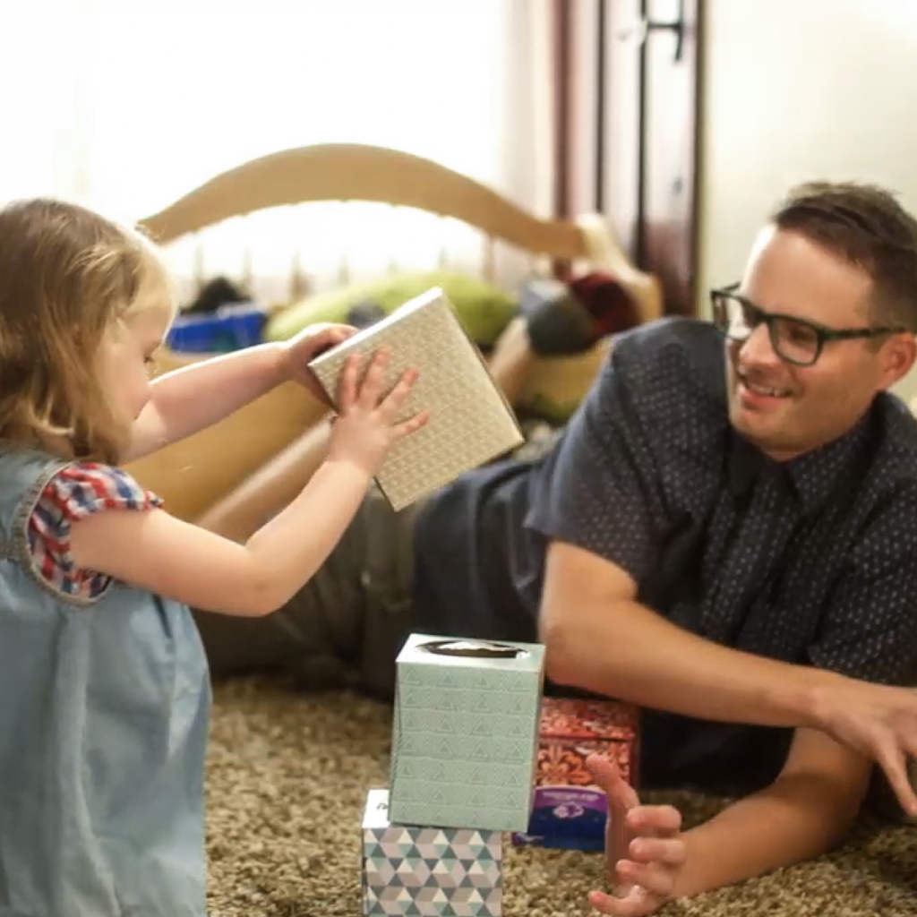 young girl playing with dad and tissue boxes