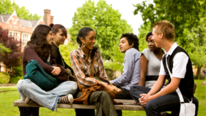 A group of young adults sitting on a bench outside