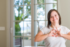Smiling young woman with Down syndrome making a heart sign with her hands