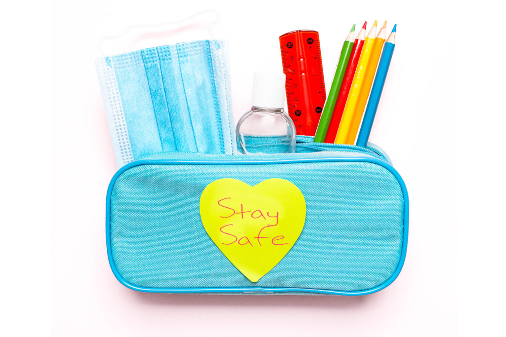 light blue pencil case containing mask and supplies with 'stay safe' heart shaped post it on front