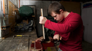 Teenager with Down syndrome placing wood in a vice in a workshop