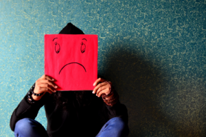 person sitting and holding a red piece of paper with a sad face drawn on it in front of their face