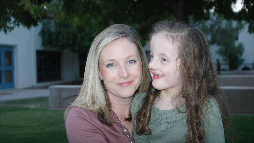 Blonde mom next to young daughter with long curly hair