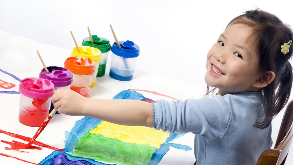 preschool girl painting with multiple colors