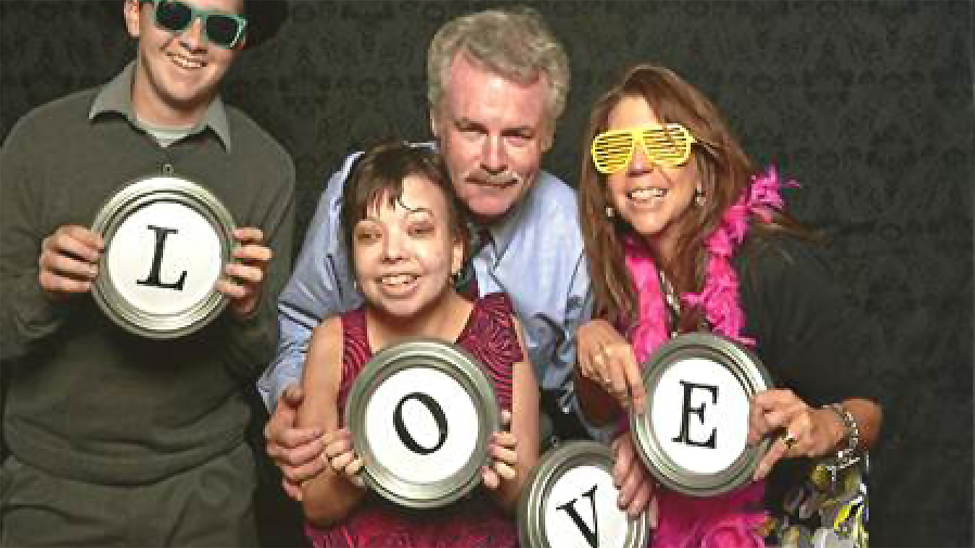 Family having fun in photo with props spelling out LOVE