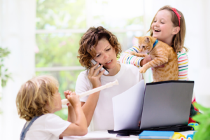 Busy mom trying to work while two busy kids distract her
