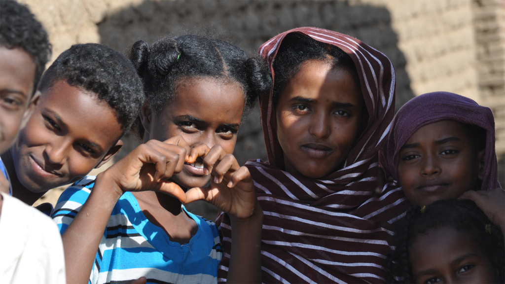 Young dark skinned children one girl making a heart with her hands