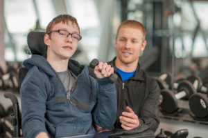 Young man in wheelchair assisted by therapist
