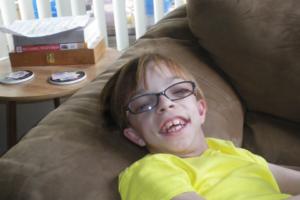 smiling tween girl laying on sofa