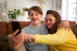 Young couple with Down syndrome sitting on sofa taking a selfie