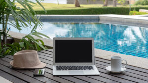laptop and coffee cup on a table next to a pool