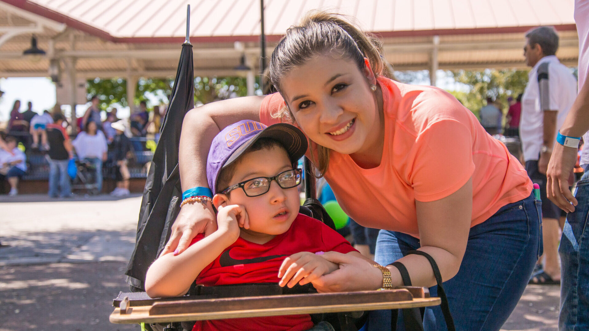 young mom with arm around son who is in a wheelchair