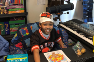 Young smiling boy in his room surrounded by books toys keyboard telescope