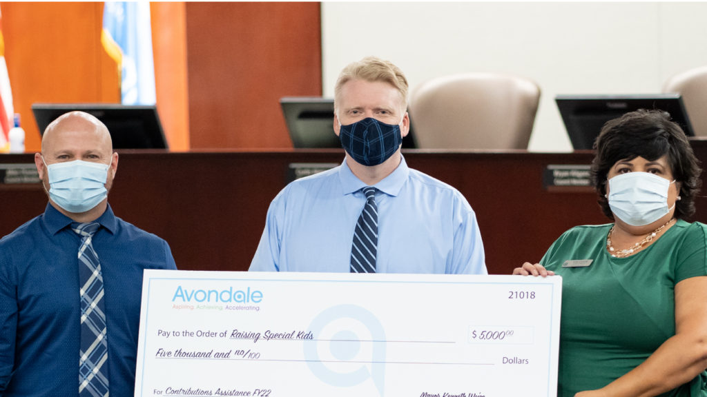 Three adults holding large donation check for Raising Special Kids
